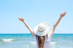 Young Pretty Caucasian Woman with Long Chestnut Hair in Hat Hands Lifted up in the Air Stands at Beach Looks at Turquoise Sea. Horizon on Blue Sky Background stock photos