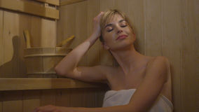 Young pretty caucasian woman relaxing in sauna. Stock Photography