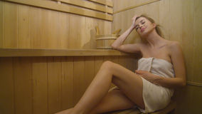 Young pretty caucasian woman relaxing in sauna. Attractive blond hair woman relaxing in beauty SPA Stock Photos