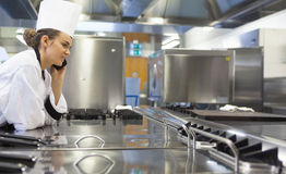 Young pretty chef standing next to work surface phoning Royalty Free Stock Image