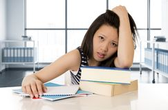 Young pretty chinese asian student woman working paperwork and books tired and bored. In frustrated and unhappy face expression in university exams and stress Stock Images