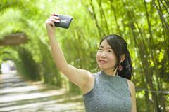 Young pretty Chinese Asian woman enjoying having fun taking selfie picture with mobile phone camera posing cool Stock Image