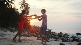 Young pretty couple dancing a slow dance on tropical beach at sunset time. slow motion. 1920x1080. Young cheeful couple dancing a slow dance on tropical beach at stock video