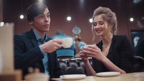 Young pretty couple drinking coffee, discussing and laughing in a modern cozy café on a date. Young pretty couple drinking coffee, discussing and laughing in a stock video