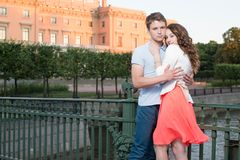 Young pretty couple embracing on the bridge near historical palace. Stock Photo