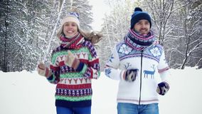 Young pretty couple jogging together in the winter forest stock video footage