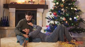 Young pretty couple lying at the Christmas tree together. New Year and Christmas concept. Young pretty couple lying at the Christmas tree together. New Year and stock footage