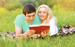Young pretty couple together reading a book together. On the grass Stock Photography