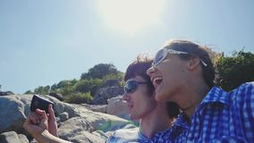 Young pretty couple wearing sunglasses taking selfie portrait by beautiful mountain with lense flare effects. Slow. Young couple taking selfie portrait by stock video