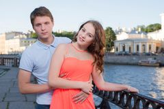Young pretty curl brunette and her boyfriend stand on the city river embankment Royalty Free Stock Image