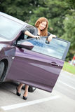 Young pretty curly haired woman standing behind a car Royalty Free Stock Photography