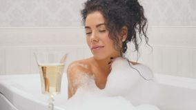 Pretty lady in the bath. Young pretty curly woman is in the bathroom. Brunette handsome lady sits in the bath with a lot of foam and the glass of champagne stock footage