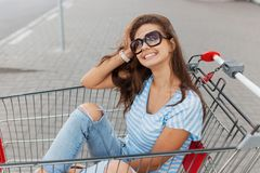 A young pretty dark-haired girl with glasses,wearing casual style,is sitting in a grocery cart near the shop. stock images