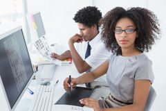 Young pretty designer looking at camera at her desk Royalty Free Stock Photography
