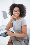 Young pretty designer smiling at camera at her desk Stock Images
