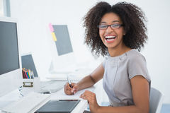 Young pretty designer smiling at camera at her desk Royalty Free Stock Photo