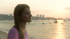 Young pretty dreamy woman in pink t-shirt on beach sea sunset boats cityscape at background. Young pretty woman in pink t-shirt sitting thinking alone on beach stock footage