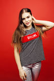Young pretty emitonal posing teenage girl on bright red background, happy smiling lifestyle people concept. Close up royalty free stock photography