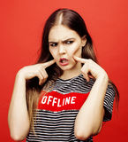 Young pretty emitonal posing teenage girl on bright red background, happy smiling lifestyle people concept. Close up stock photography