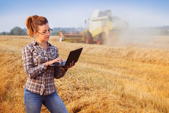 Young pretty farmer girl in glasses in wheat field. Young pretty farmer girl in glasses with hair tied in a ponytail make notes on notebook in wheat field while Stock Photo