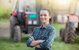 Farmer woman with tractors on farmland. Young pretty farmer woman standing on farmland with crossed arms and tractors in background Royalty Free Stock Images