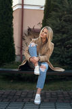Young pretty fashionable blonde woman dressed in ripped jeans and white sweater. Sitting on the ground in summer and having fun Royalty Free Stock Images