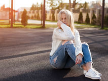 Young pretty fashionable blonde woman dressed in ripped jeans Stock Photos
