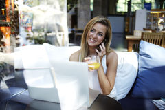 Young pretty female with beautiful smile having talking conversation during work on laptop computer. Happy woman speaking on mobile phone while sitting at the Stock Images