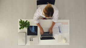 Young pretty female doctor working with notebook in the office. stock video