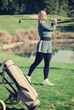 Young pretty female golf player is succeeded in ball hitting Stock Photo