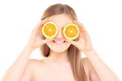 Young pretty female holding an orange half in front of her eyes Royalty Free Stock Photography