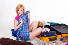 Young pretty female packing her suitcase before Royalty Free Stock Photo