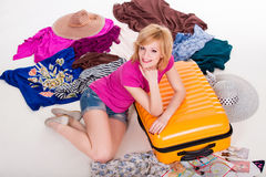 Young pretty female packing her suitcase before Royalty Free Stock Images
