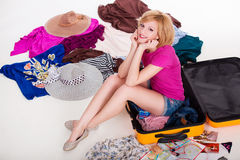 Young pretty female packing her suitcase before Stock Image