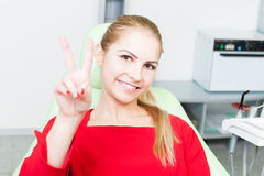 Young and pretty female patient at dentist showing victory gestu Stock Photo