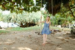 Young pretty female person wearing jeans dress and riding on swing, sand in background. royalty free stock image