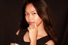Young pretty Filipina model looking at the camera. With dak background Royalty Free Stock Photography