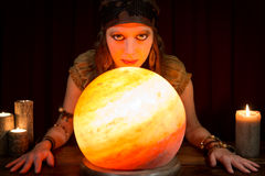 Young pretty fortune teller with a shining crystal ball and cand Royalty Free Stock Photos