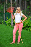 Young pretty gardening woman with rakes. Outdoor Stock Photography