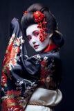 Young pretty geisha in kimono with sakura and Royalty Free Stock Photos