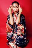 Young pretty geisha on red background posing in kimono, oriental people concept Stock Photos