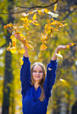 Young pretty girl. Throwing autumn leaves royalty free stock photos
