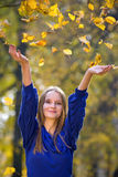 Young pretty girl. Throwing autumn leaves royalty free stock images