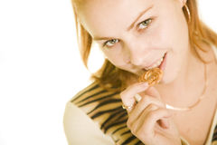 Young pretty girl bites a cake Stock Image