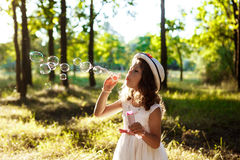 Young pretty girl blowing bubbles, walking in park at sunset. Stock Photography