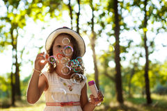 Young pretty girl blowing bubbles, walking in park at sunset. Stock Image