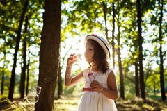 Young pretty girl blowing bubbles, walking in park at sunset. Stock Photos