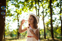 Young pretty girl blowing bubbles, walking in park at sunset. Royalty Free Stock Photography