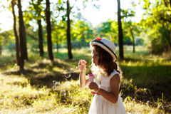 Young pretty girl blowing bubbles, walking in park at sunset. Royalty Free Stock Images