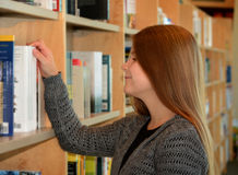 Young pretty girl browsing books. She enjoys her activity Royalty Free Stock Photography